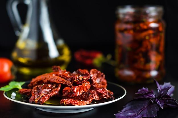 Il processo di cottura dei pomodori secchi in una ciotola con olio d'oliva. vaso di vetro con verdure, ingredienti e spezie per uno spuntino sulla superficie nera