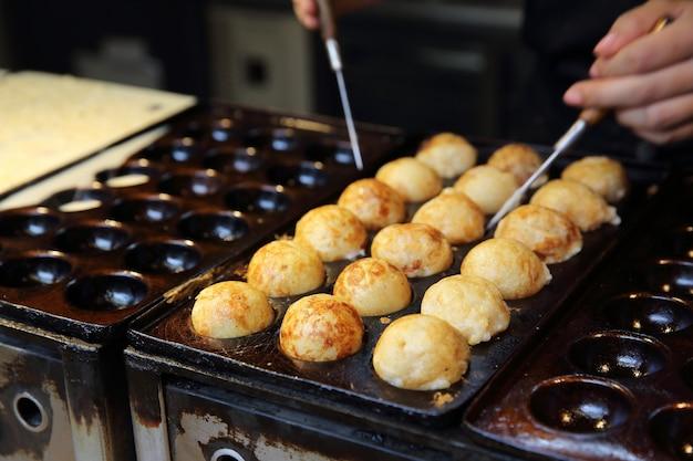 Processo per cucinare il cibo giapponese takoyaki