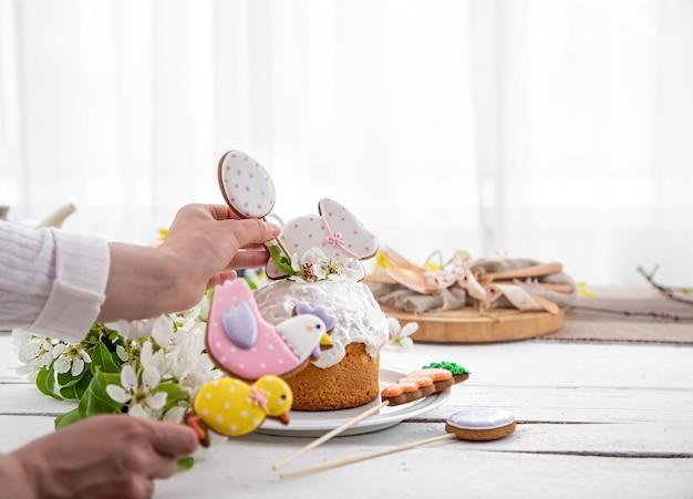 Il processo di decorazione di una torta festiva. il concetto di preparazione per le vacanze di pasqua.
