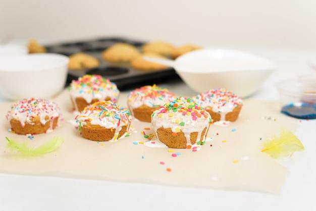 Processo di decorazione di mini cupcakes torte pasquali con glassa bianca e caramelle dolci, vista dall'alto, rami di salice e uova da colorare.