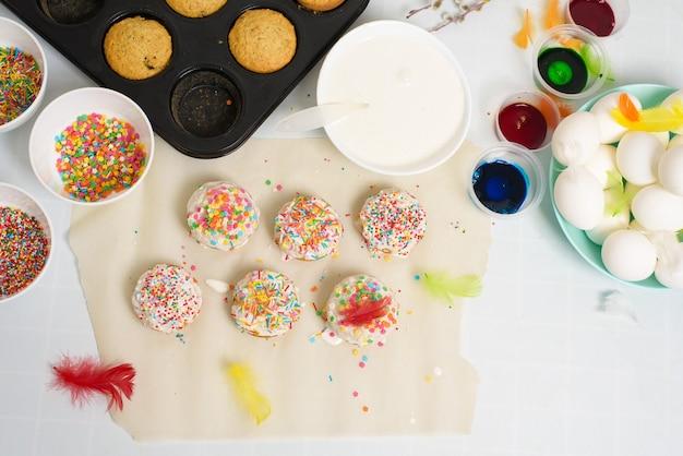 Il processo di decorazione dei mini cupcakes delle torte pasquali con glassa bianca e caramelle dolci
