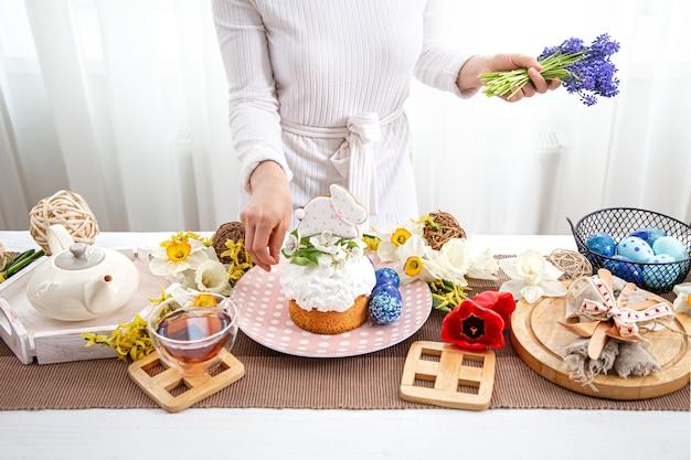 Il processo di decorare con fiori una tavola festiva di pasqua con dolcetti.
