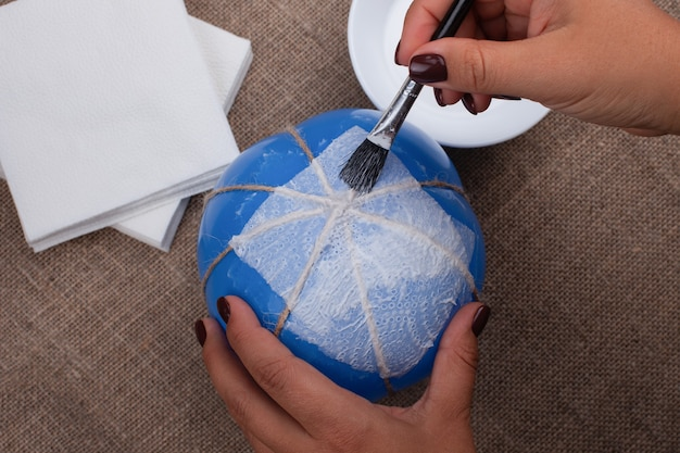 Il processo di incollaggio dei tovaglioli su un palloncino, creando una zucca di cartapesta.