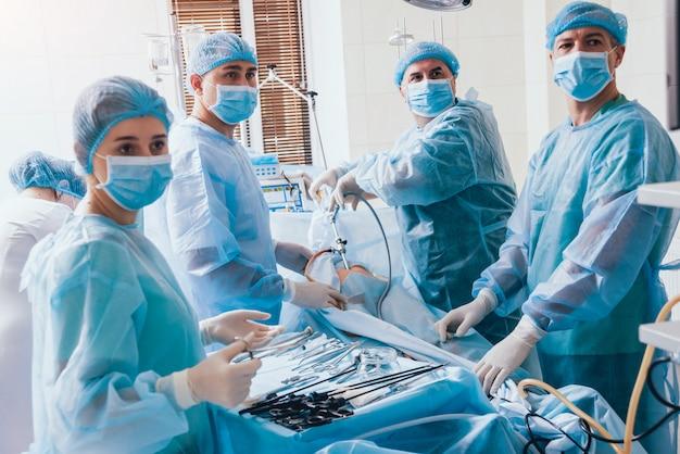 Processo di chirurgia ginecologica mediante apparecchiature laparoscopiche. gruppo di chirurghi in sala operatoria con apparecchiature chirurgiche