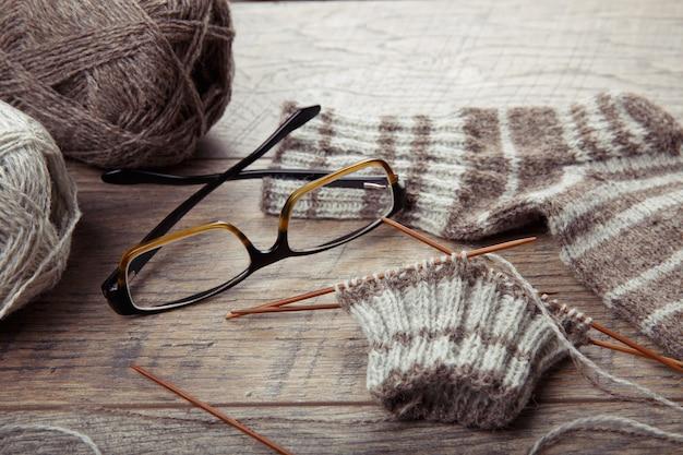 Il processo di lavorazione del calzino con ferri da maglia circolari in bambù, occhiali, filati di lana di colore naturale, bicchieri su un tavolo rustico in legno.