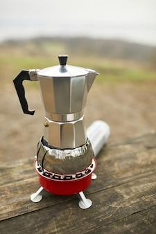 Processo di preparazione del caffè da campeggio all'aperto con caffettiera geyser in metallo su un bruciatore a gas