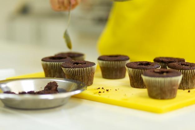Il processo di preparazione di cupcake al cioccolato con panna dolce. creazione di torte da pasticceri professionisti