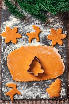 Il processo di preparazione dei biscotti allo zenzero di natale. stampo a forma di albero di natale su pasta cruda per biscotti di panpepato.