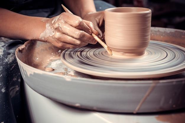 Il processo di creazione di una brocca di argilla su un tornio da vasaio. avvicinamento.