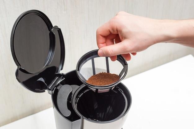 Processo di preparazione del caffè da chicchi macinati in una caffettiera - installazione di un filtro di plastica con caffè macinato.