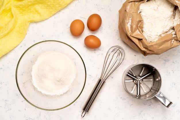 Il processo di preparazione dell'impasto per frittelle con ingredienti su un tavolo luminoso, uova e farina vengono montati con un mixer.