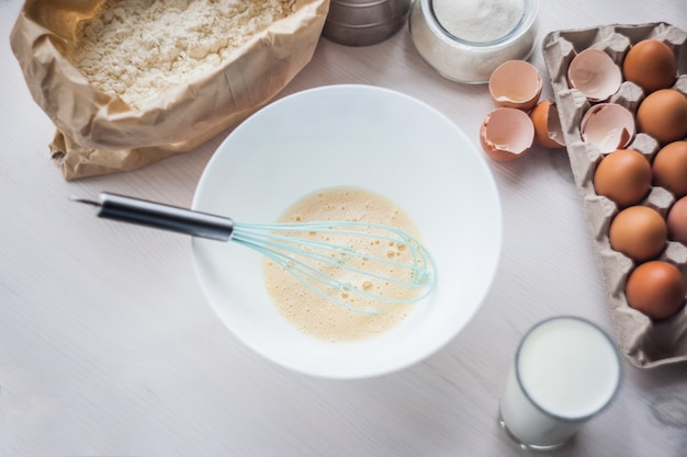 Processo di fare l'impasto, la mano della donna frusta le uova e la farina in una ciotola