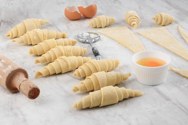 Processo di preparazione del croissant fatto in casa, preparazione del croissant crudo al forno a casa. croissant di varie dimensioni sopra il tavolo in marmo bianco