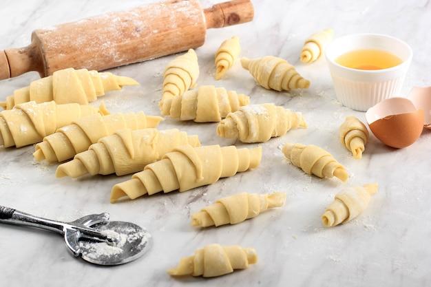 Processo di produzione di croissant fatti in casa, croissant di varie dimensioni sopra un tavolo in marmo bianco