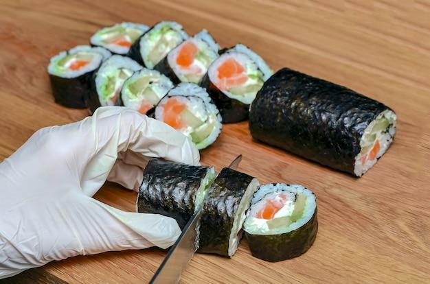 Il processo di preparazione del sushi giapponese. il coltello in mano taglia un primo piano del rotolo su una tavola di legno.