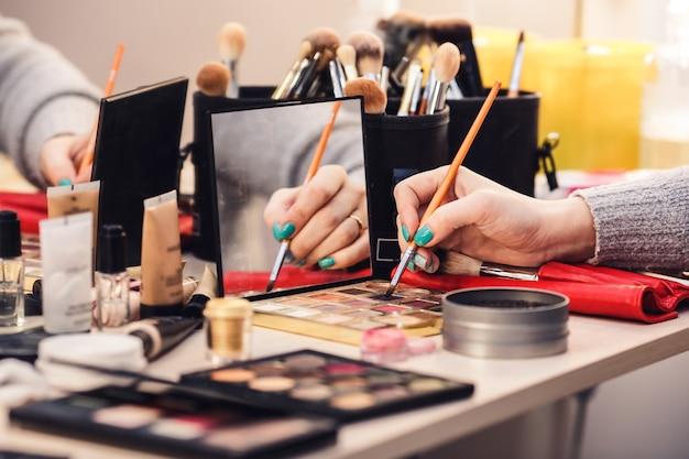 Processo di realizzazione del trucco. la truccatrice applica l'ombretto sul pennello. accessori per il trucco sul tavolo in studio