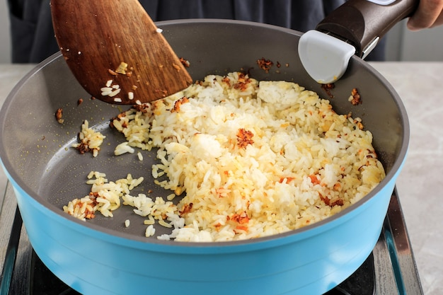 Processo di preparazione del nasi goreng (riso fritto), riso tostato su una padella di ceramica usando una spatola di legno