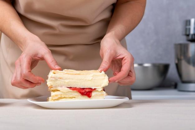 Processo di preparazione della torta con ripieno di vaniglia e frutta. il pasticcere sta preparando la torta.