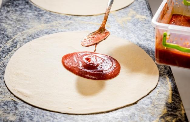 Il processo di preparazione della pizza. mani del panettiere del cuoco unico che producono pizza alla cucina del caffè