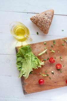 Il processo di produzione di insalata a casa su uno sfondo bianco. il vegetarianismo. uno stile di vita sano.
