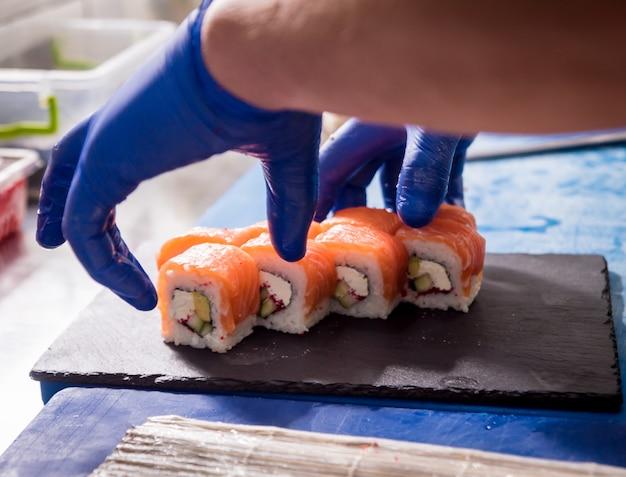 Processo di produzione di sushi e involtini alla cucina del ristorante. mani da chef con coltello.
