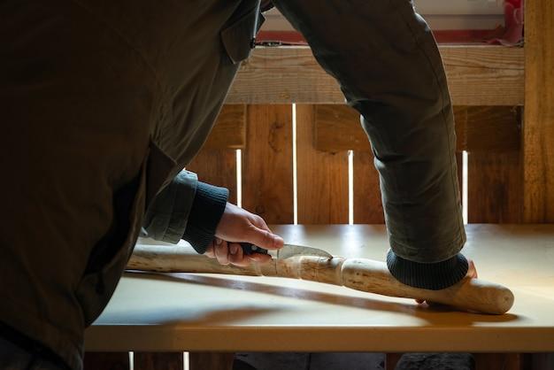 Processo dell'uomo che fa il bastone da passeggio in legno all'interno durante la quarantena. intagliare un bastone di legno sul tavolo usando un coltello