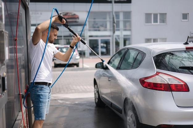 Processo dell'uomo che lava la sua auto in una stazione di autolavaggio self-service
