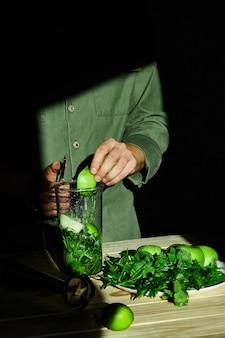 Processo di preparazione del frullato di disintossicazione verde con il frullatore, mele tagliate giovane