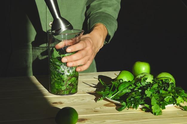 Processo di preparazione del frullato verde di disintossicazione con il frullatore, mani del giovane che cucinano frullato sano con frutta fresca e spinaci verdi. concetto di disintossicazione stile di vita. bevande vegane