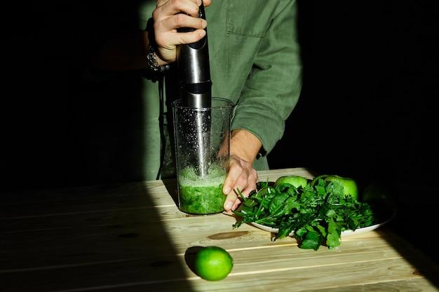 Processo di preparazione del frullato verde della disintossicazione con il miscelatore, mani del giovane che cucinano frullato sano.