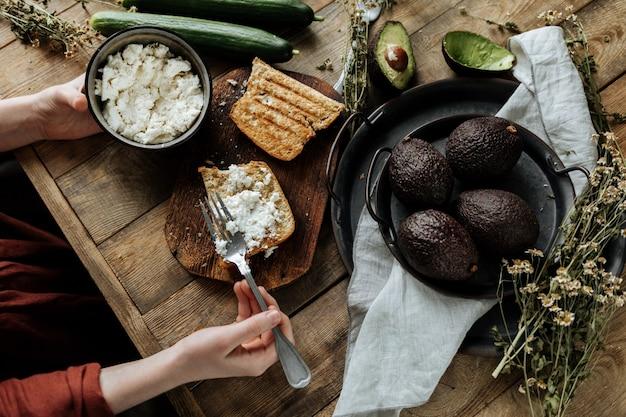 Il processo di preparazione di una sana colazione a base di pane, ricotta e avocado su un tavolo di legno.