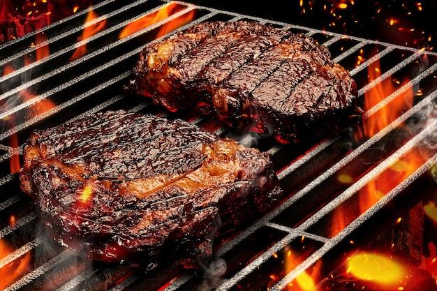 Processo di preparazione di due bistecche di maiale o di manzo. carne arrostita su barbecue estivo portatile in metallo griglia per barbecue con fuoco fiammeggiante brillante, fumo e carbone di legna. concetto di cucina e ristorante. avvicinamento