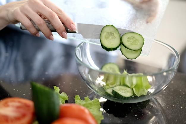 Processo di preparazione di un'insalata di verdure, spostando le fette di cetriolo nella ciotola di vetro. mangiare sano e stile di vita vegano