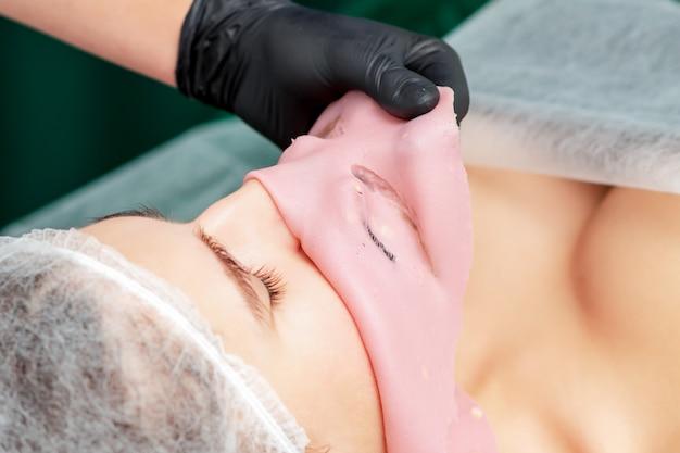 Processo di rimozione della maschera di alginato facciale dal viso di donna da vicino.
