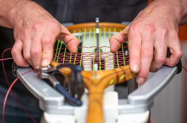 Processo di incordatura di una racchetta da tennis storica o retrò in un negozio di tennis, sport e concetto di tempo libero