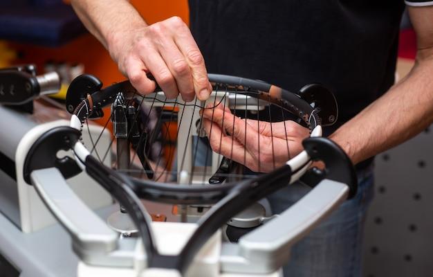 Processo di incordatura di una racchetta da tennis in un negozio di tennis, sport e concetto di tempo libero