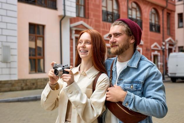 Elaborare o scattare foto del centro storico da parte di fotografi viaggiatori. coppia viaggia insieme. ritratto di vista laterale di un bell'uomo e di una donna caucasici in abbigliamento casual che si godono il viaggio nella nuova città