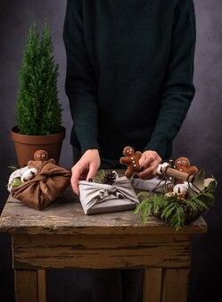 Processo di confezionamento della confezione regalo natalizia eco friendly furoshiki