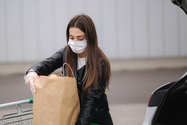 Un processo di giovane donna attraente che prende la spesa da un supermercato dal carrello all'auto