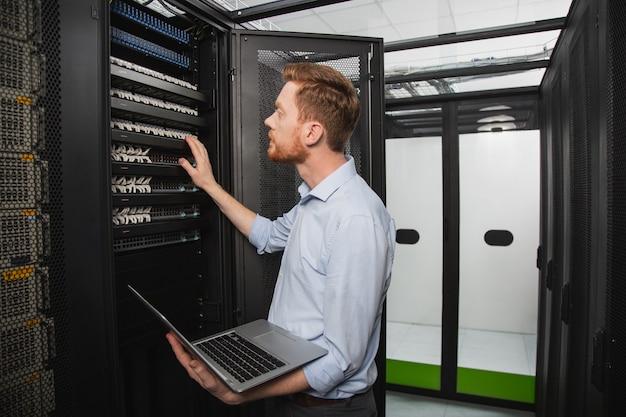 Sistema di elaborazione. tecnico it concentrato che esamina l'armadio del server mentre tiene il laptop
