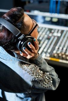 Produttore che ascolta la traccia audio in studio