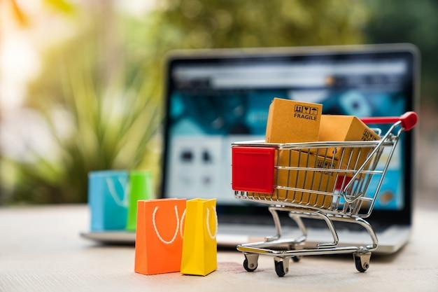Scatole del pacchetto del prodotto nel carrello con borsa della spesa e computer portatile