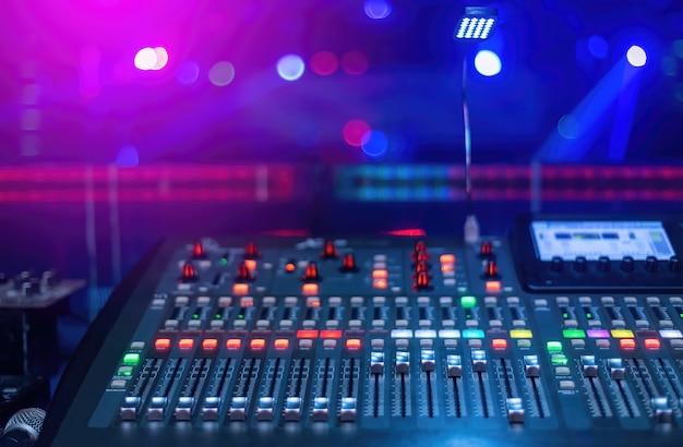 Concetto di produzione al concerto, un mixer per mixare la musica ha molti pulsanti con uno sfondo sfocato nei toni del rosa e del blu.