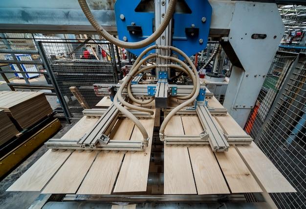 Linea di produzione della fabbrica di pavimenti in legno. macchina automatica per la lavorazione del legno cnc. Foto Premium