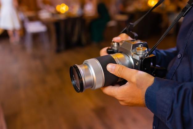 Concetto di video di film di produzione: videografo professionista o fotografo che tiene l'impostazione delle riprese della fotocamera mirrorless scatta foto o video per la registrazione all'aperto.