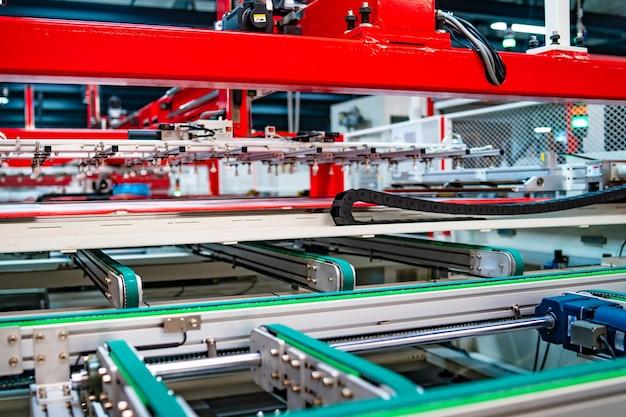 Produzione di pannelli solari, uomo che lavora in fabbrica. primo piano di macchinari speciali in fabbrica di pannelli di produzione solare