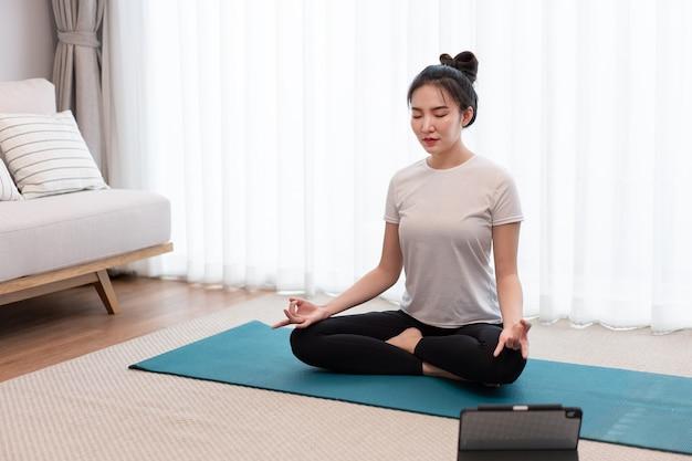 Concetto di attività produttiva una ragazza calma che si concentra sulla meditazione da sola in un'atmosfera tranquilla nel soggiorno.
