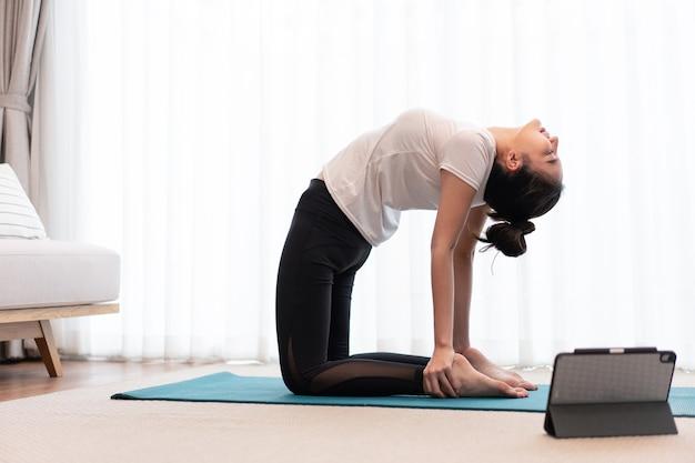Concetto di attività produttiva una giovane donna adulta che pratica la flessibilità del suo corpo facendo esercizio di pilates mat.