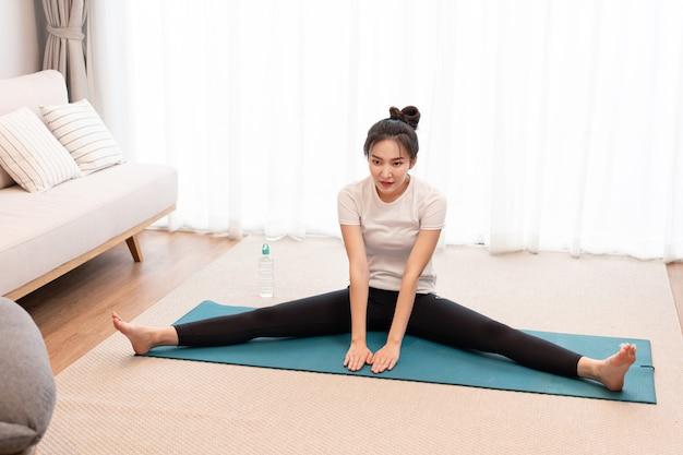 Concetto di attività produttiva una ragazza in forma seduta sul tappetino apre ogni gamba sul lato opposto e sembra concentrata sul suo esercizio.