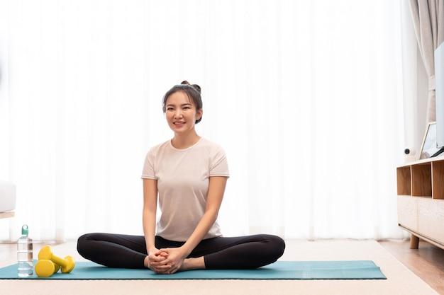 Concetto di attività produttiva una ragazza con un panino seduto sul tappeto verde rettangolare che allunga entrambe le gambe parallele al pavimento.